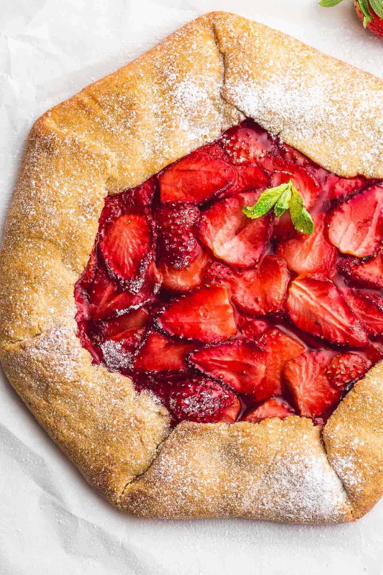 Whole strawberry galette, sprinled with powdered sugar and mint leaves