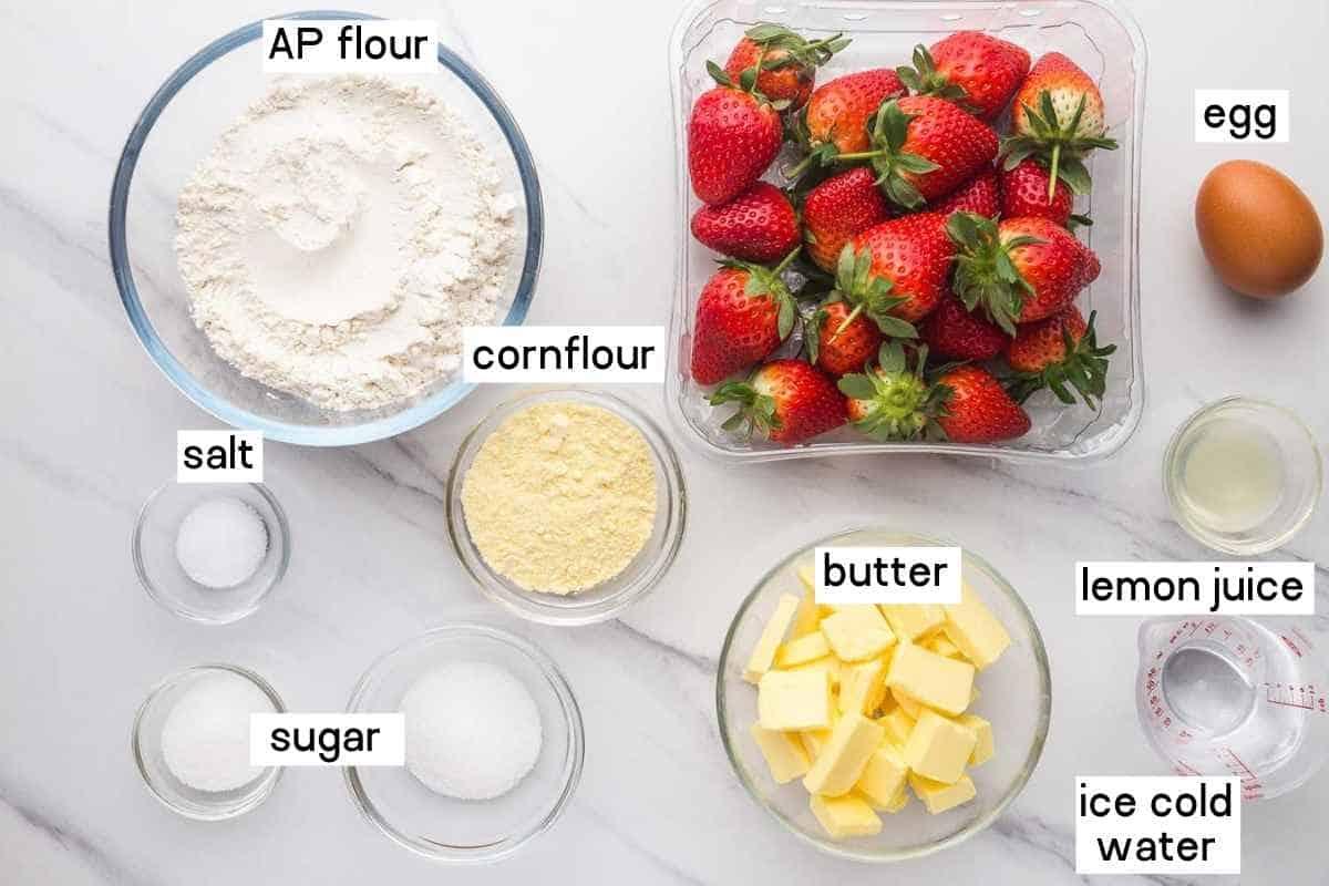 Ingredients needed to make strawberry galette including fresh strawberries, AP flour, butter, cornflour, lemon juice, salt, sugar, and water.