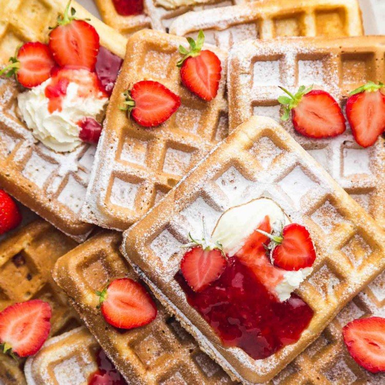 Strawberry waffles on a large white platter with a sprinkle of powdered sugar, topped with whipped cream, strawberry sauce, and fresh strawberries.