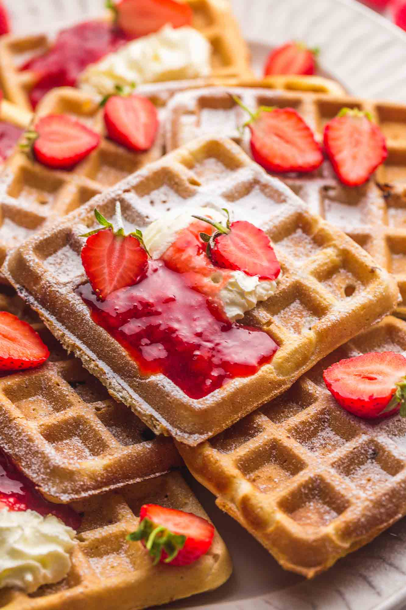 Strawberry waffles stacked randomly on a platter with strawberry sauce and fresh strawberries