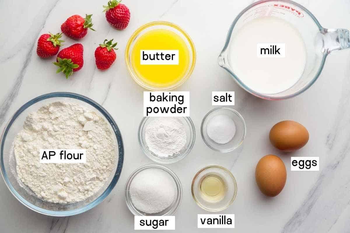 Ingredients for strawberry waffles including strawberries, flour, butter, milk, baking powder, salt, sugar, eggs and vanilla.