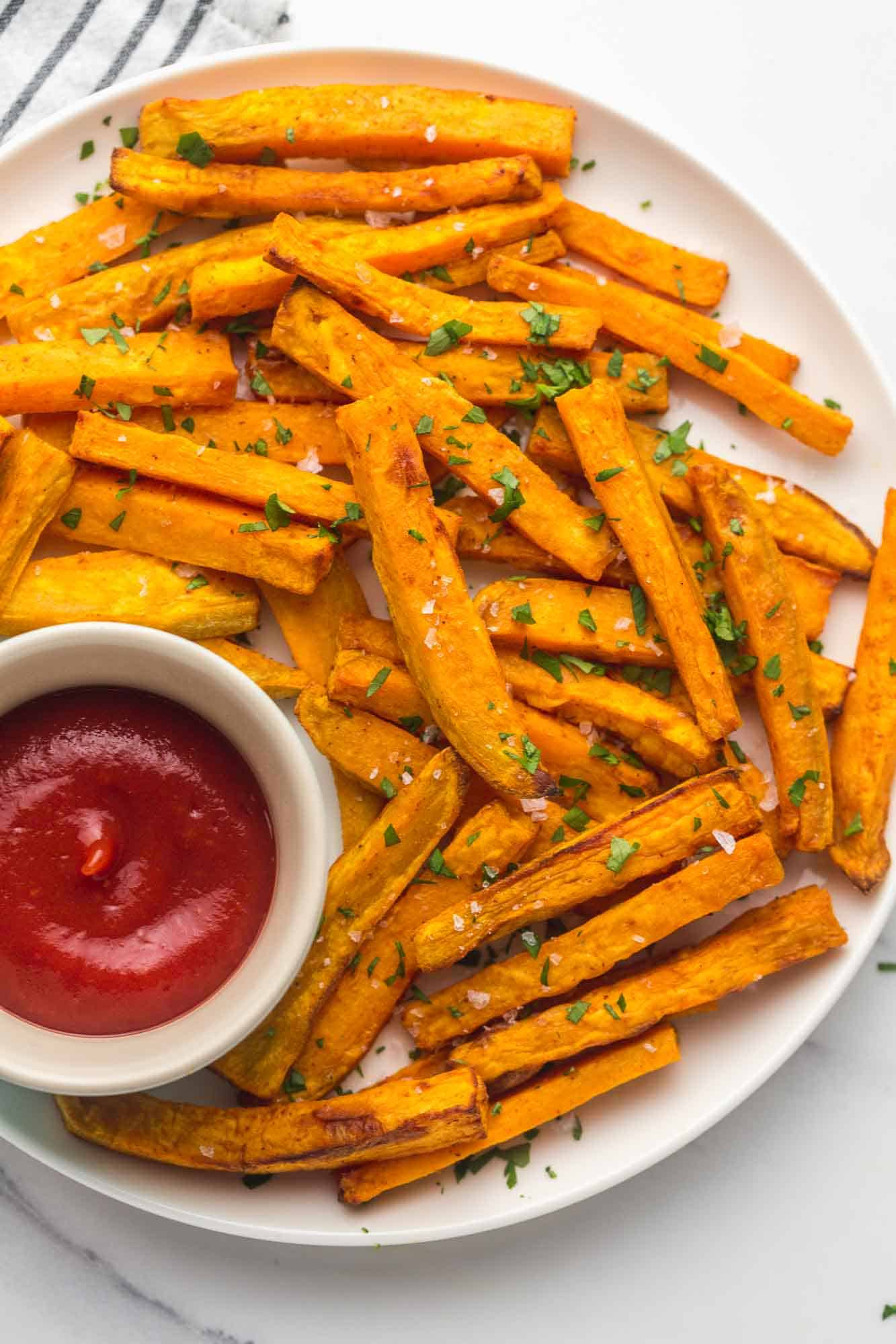 Sweet potato fries on a white plate with tomato sauce on the side