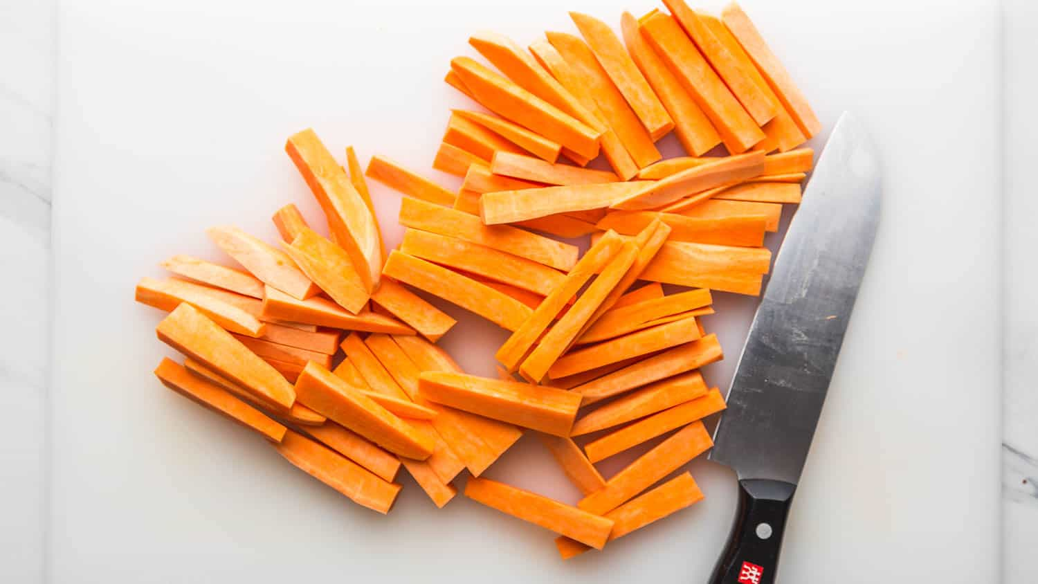 Sweet potato cut into sticks, and a Zwilling knife on the side