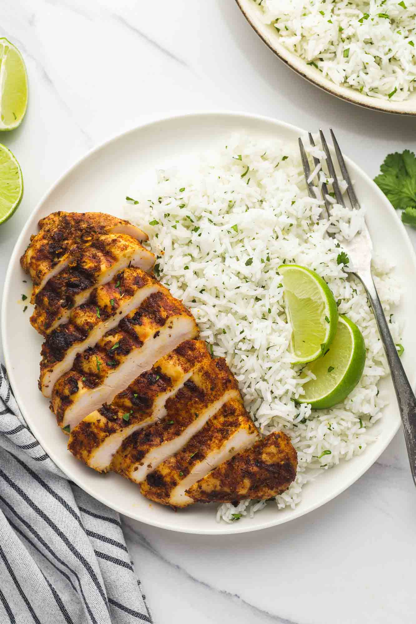 Chipotle chicken (sliced) served with cilantro lime rice in a plate with fresh lime wedges