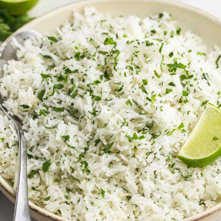 Cilantro lime rice served in a plate with fresh lime wedges