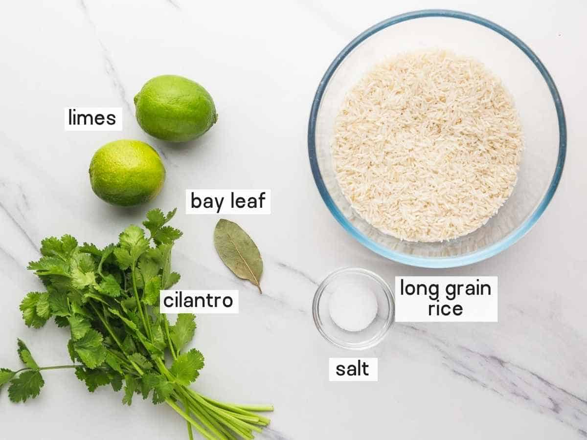 Ingredients needed to make cilantro lime rice including rice, limes, cilantro, bay leaf, and salt.