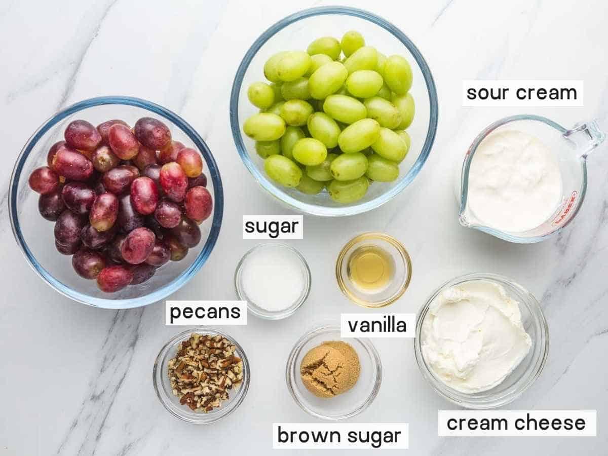 Ingredients needed to make grape salad including grapes, sour cream, cream cheese, vanilla, sugar, brown sugar, and pecans.