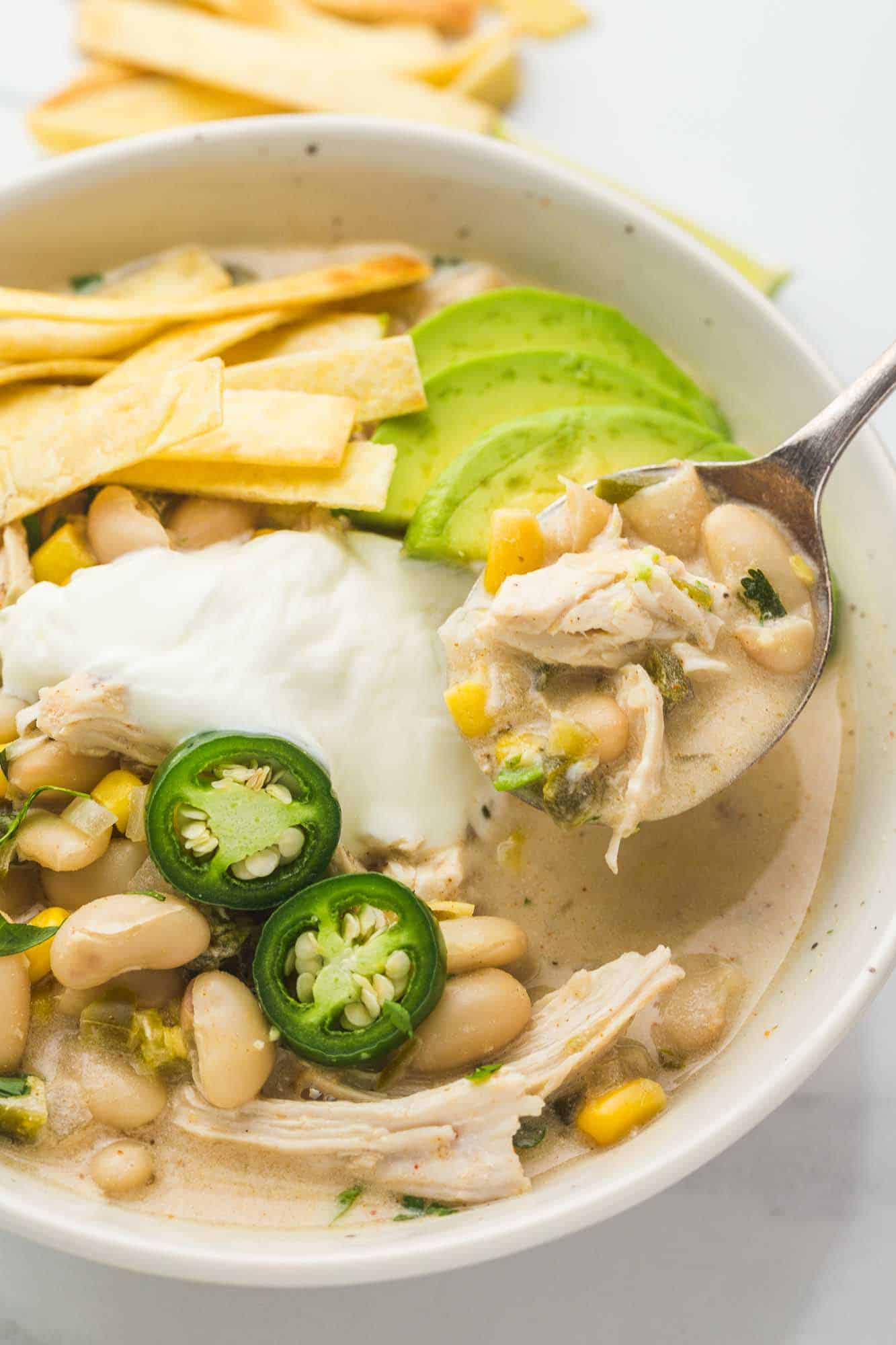 White chili in a white bowl and a spoon