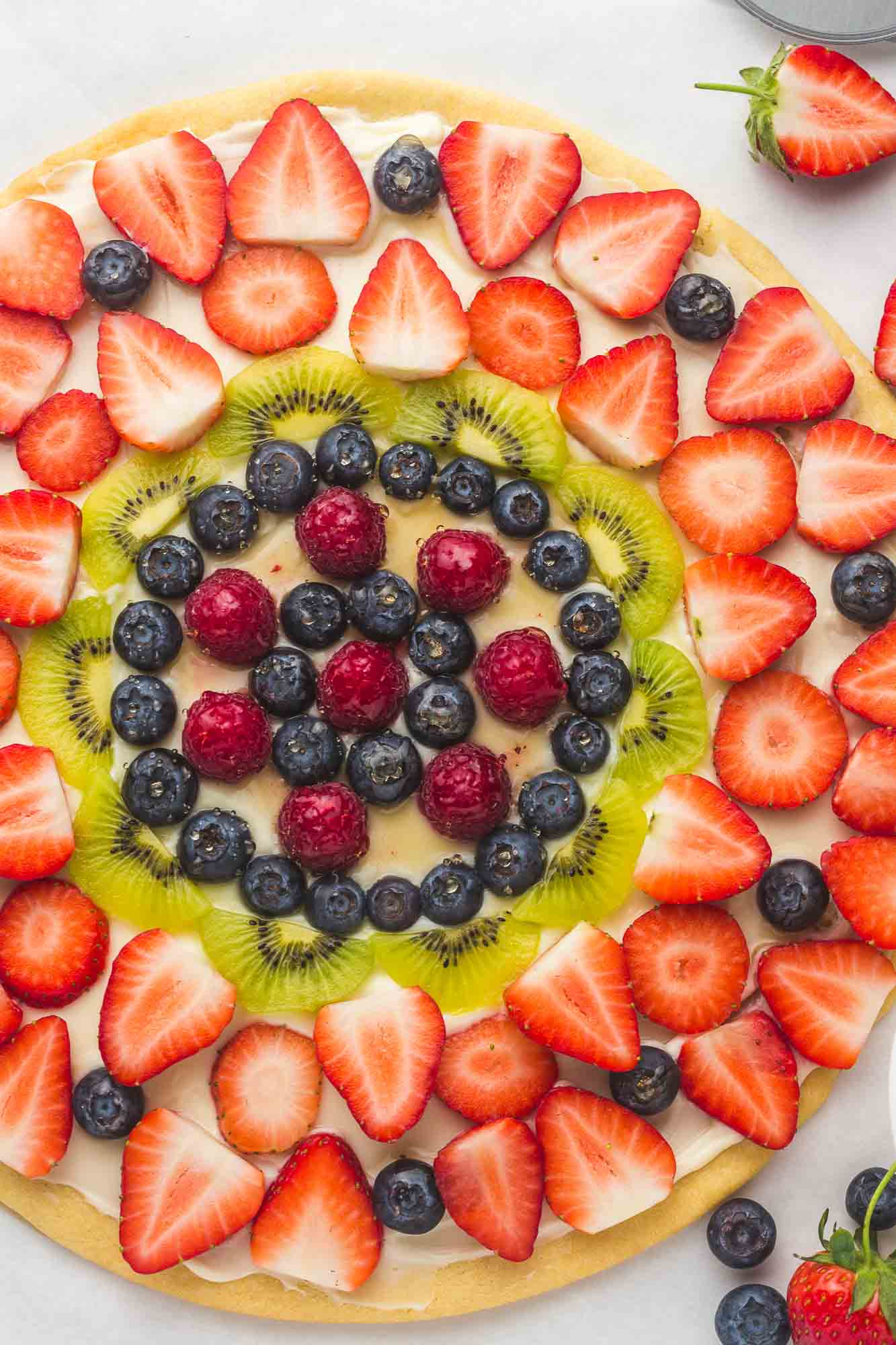 Overhead shot of a fruit pizza featuring fresh strawberries, blueberries, kiwi, and raspberries.
