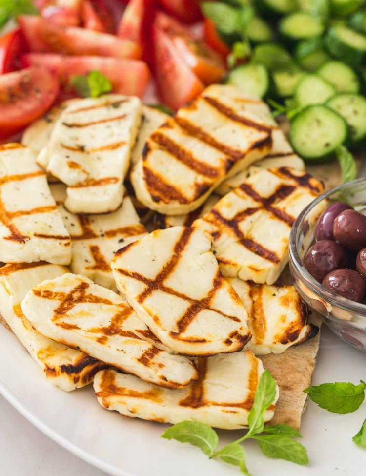 Grilled sliced halloumi on a platter with fresh cut vegetables