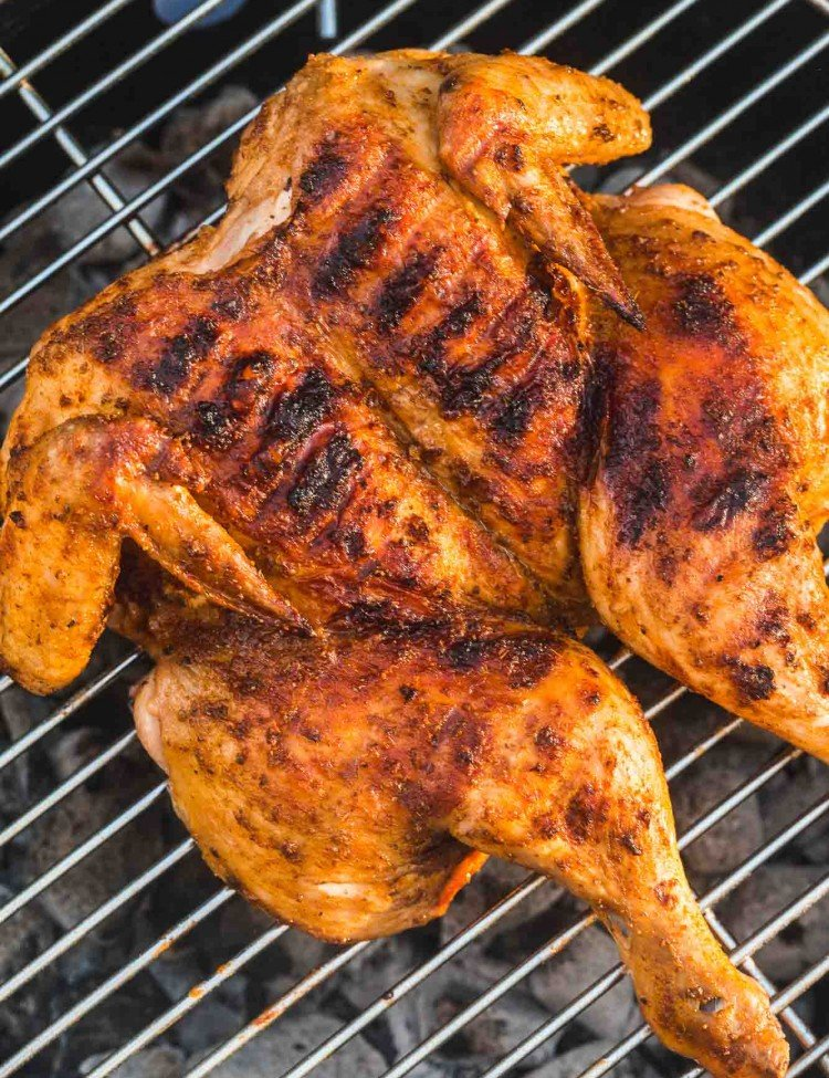 Spatchcocked grilled chicken placed on a coal grill