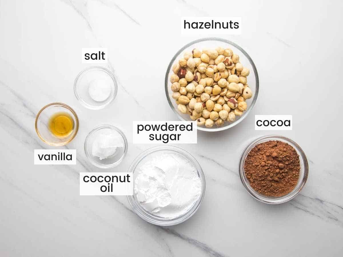 Ingredients for homemade nutella including hazelnuts, cocoa powder, powdered sugar, vanilla, coconut oil and salt.