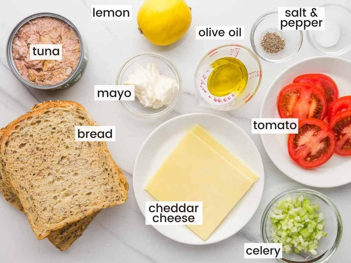 Overlay shot of ingredients needed for tuna melt including tuna, bread, cheddar cheese, lemon juice, olive oil, mayo, tomato, celery, salt and pepper.