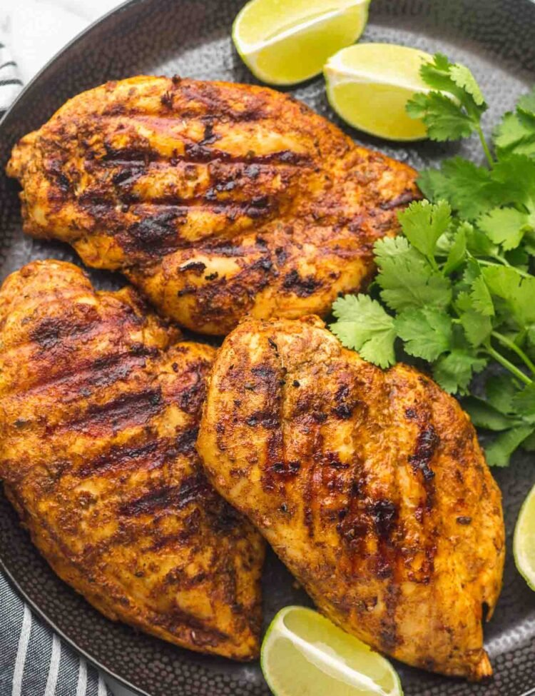 Grilled Mexican marinated chicken served on a large black plate with fresh cilantro and lime wedges