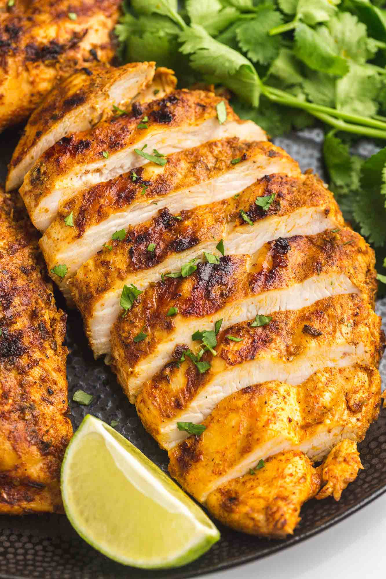 Grilled and sliced chicken breast served on a black plate with fresh lime wedge and fresh cilantro leaves