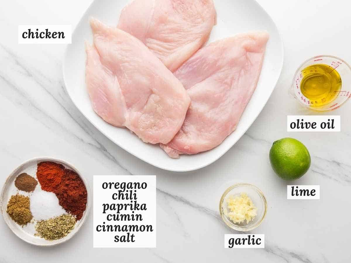 Ingredients needed to make Mexican chicken marinade including chicken cutlets, spices, lime, garlic, and olive oil