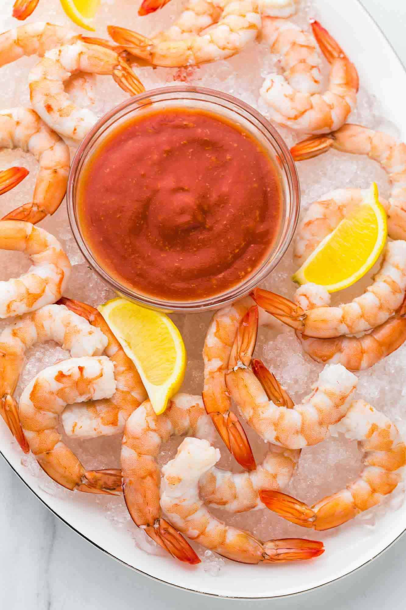 Poached shrimp served over ice on a white platter with lemon wedges and Cocktail sauce