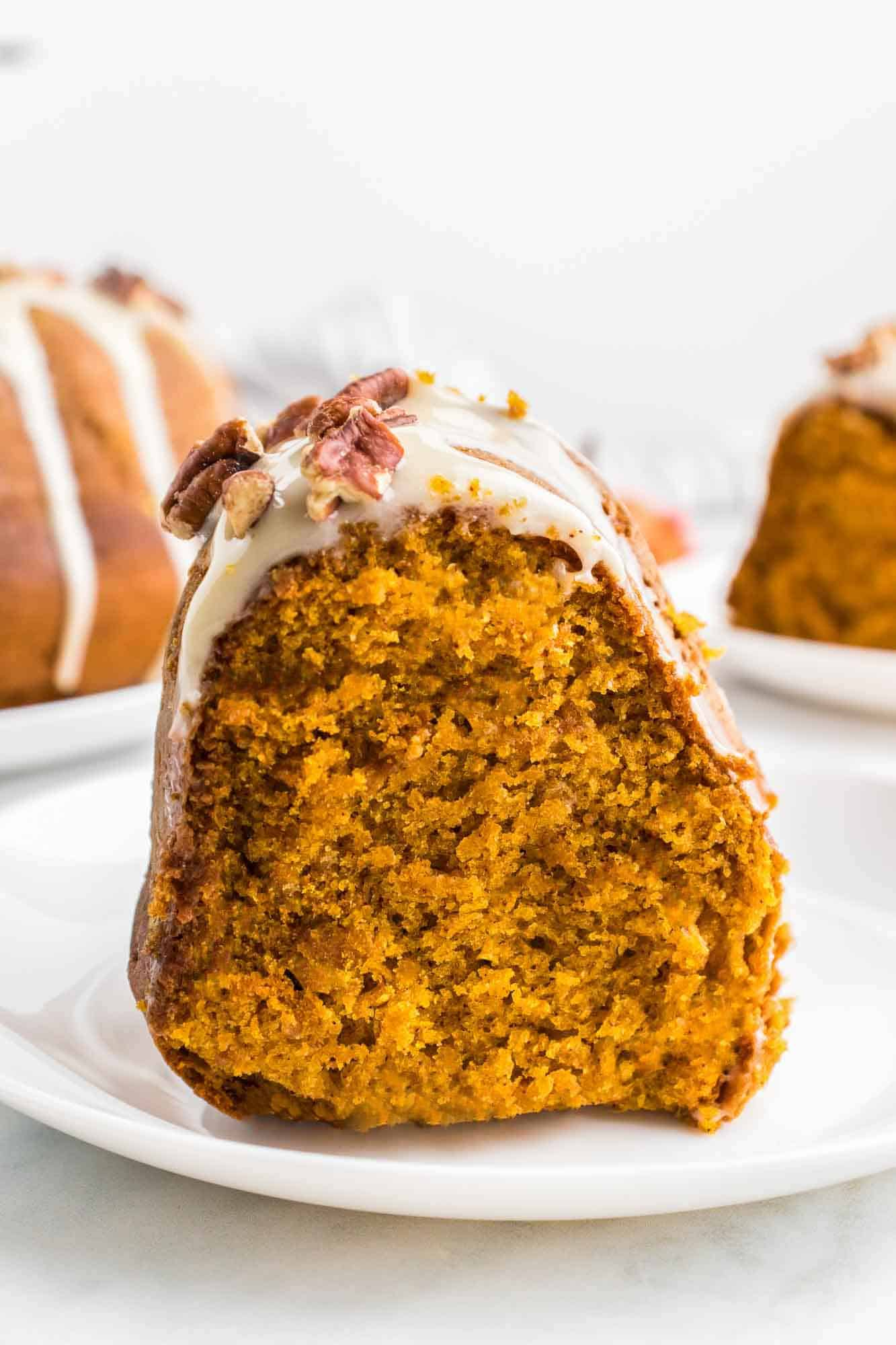 A slice of pumpkin bundt cake served on a small white plate
