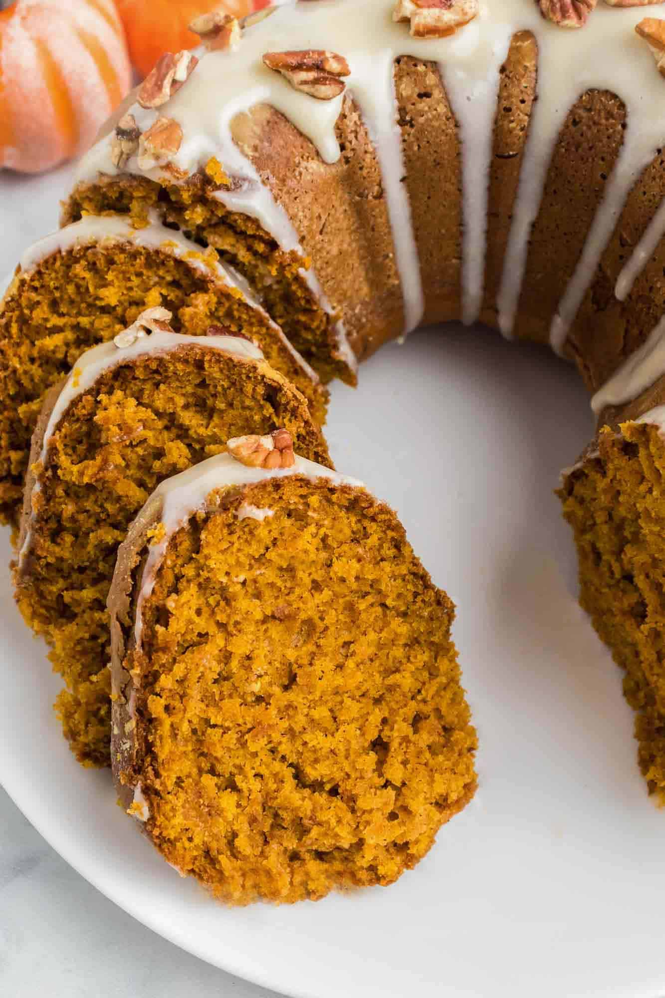 Sliced Pumpkin Bundt Cake with cream cheese frosting on top