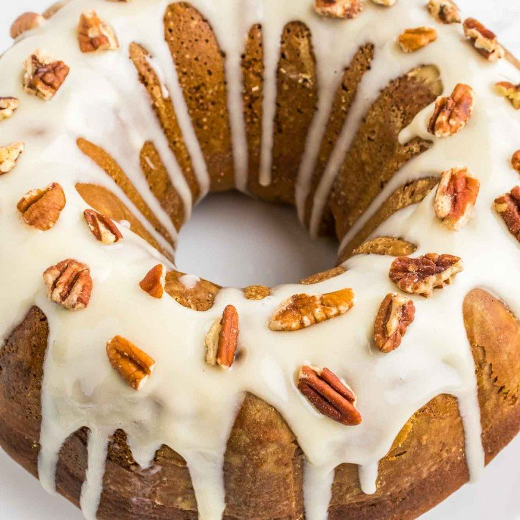 Pumpkin Bundt Cake frosted with cream cheese frosting and topped with sliced pecans
