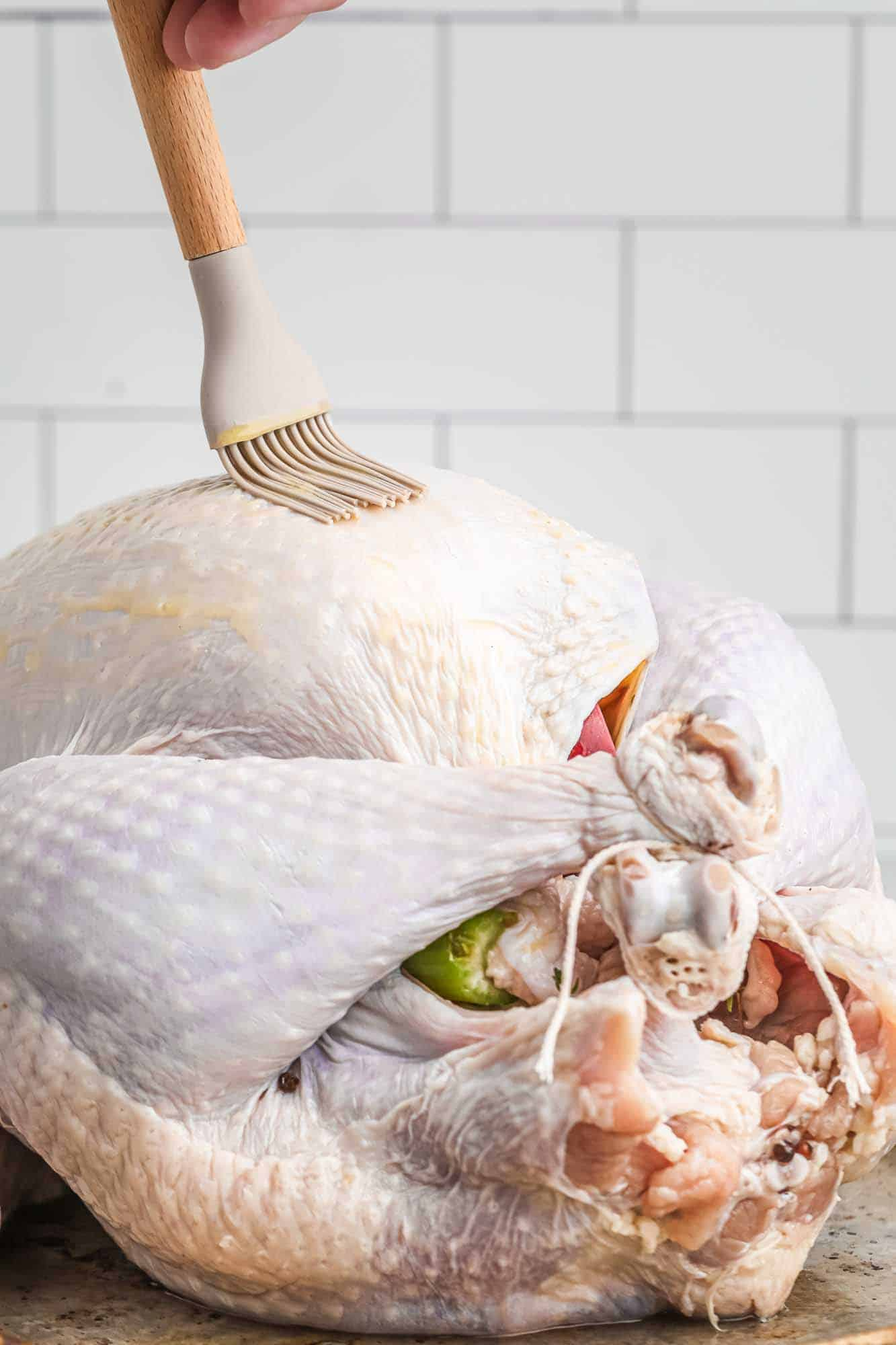 Brushing a raw turkey with melted butter