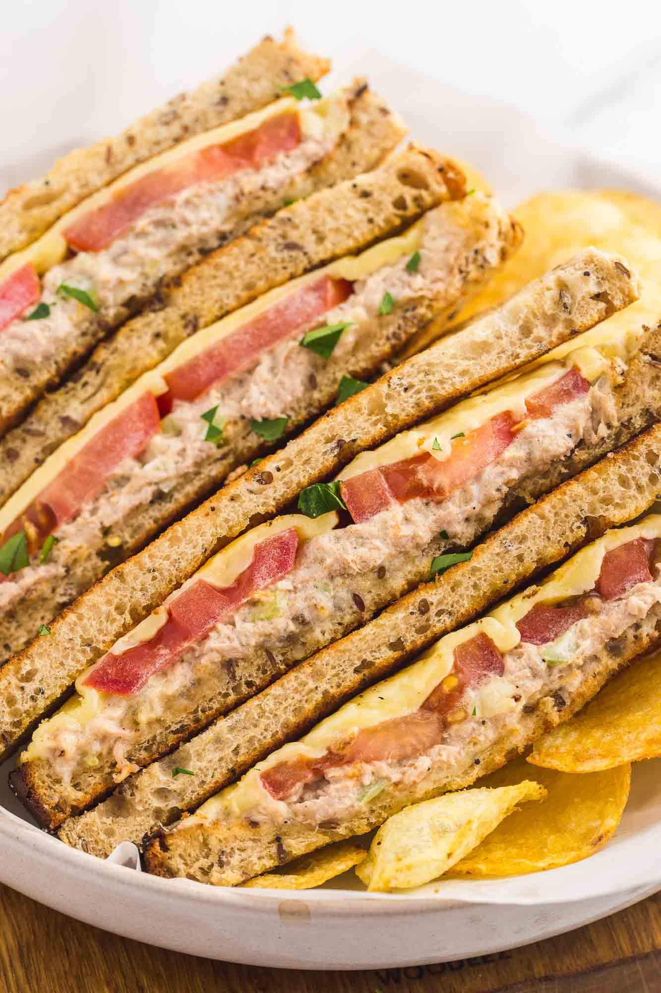 Stacked tuna melt sandwiches on a white plate
