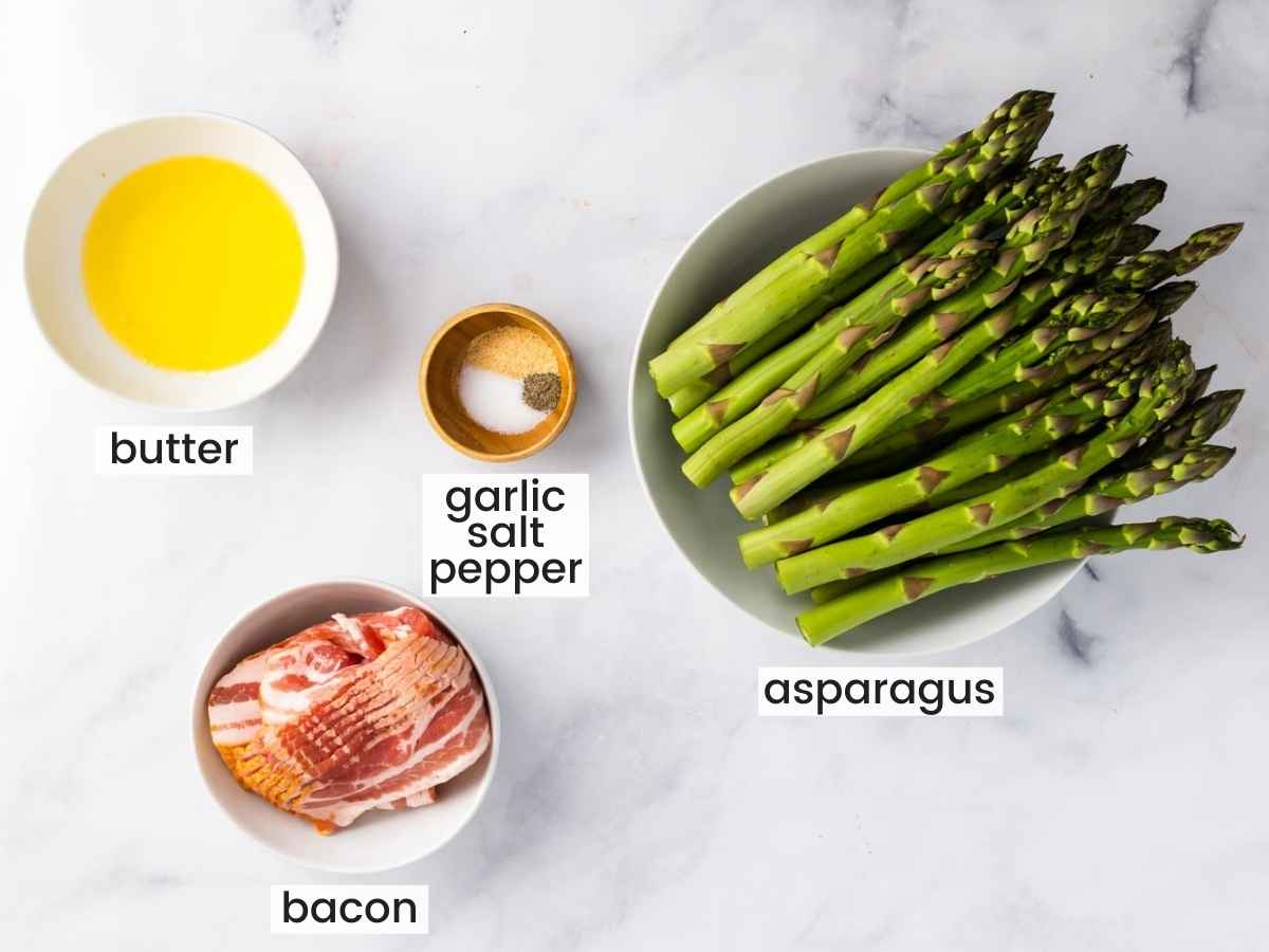 Overhead shot of ingredients including asparagus, melted butter, bacon, garlic powder, salt, and pepper.