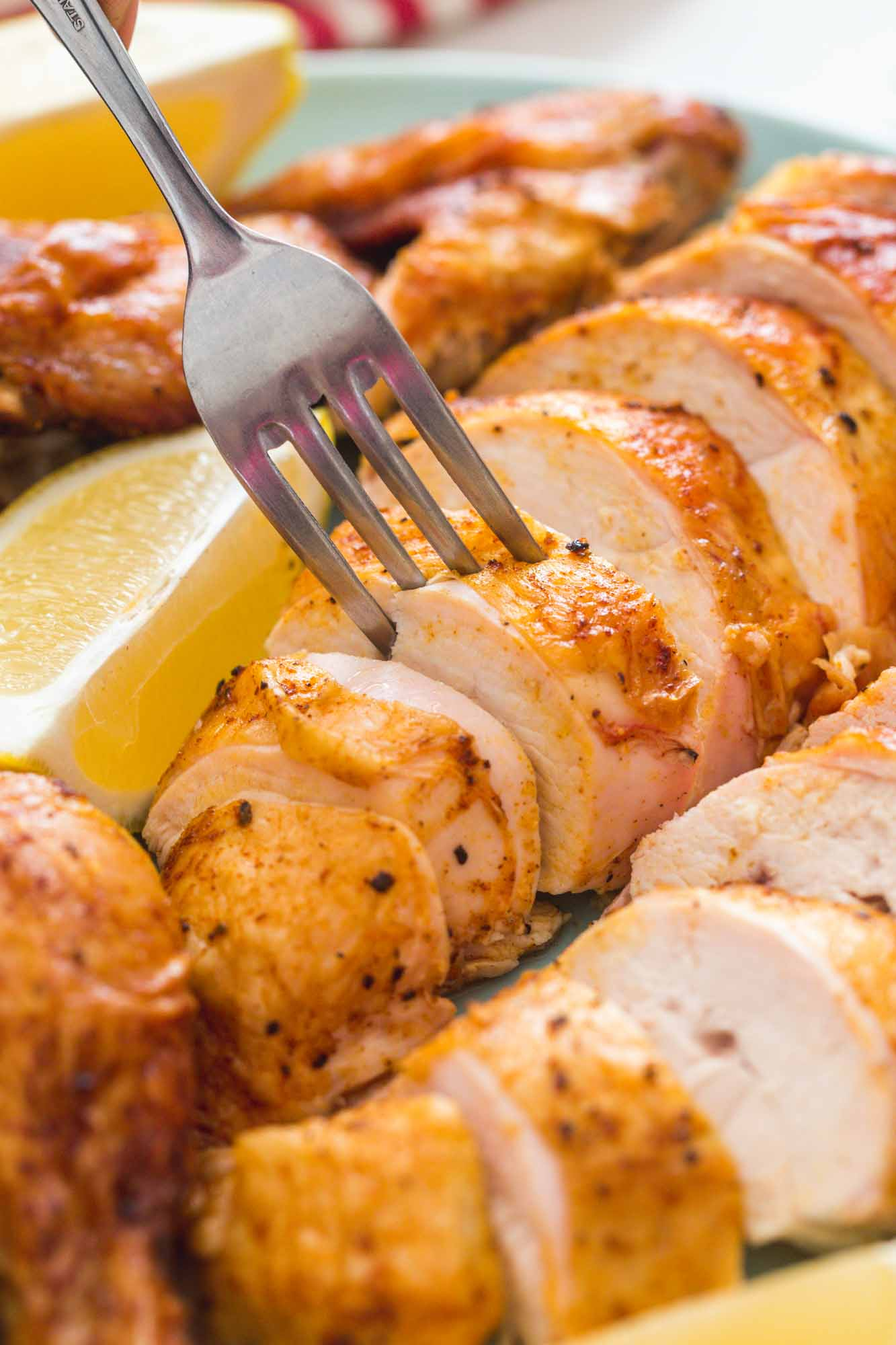 Taking a slice of crispy chicken breast that is sliced and served on a platter with lemon wedges