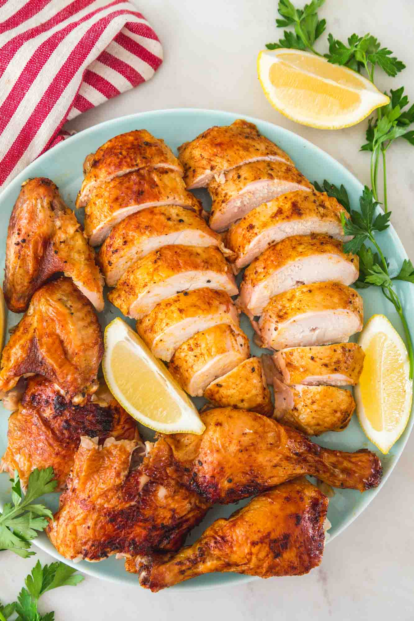 Carved chicken served on a platter with lemon wedges and fresh parsley leaves