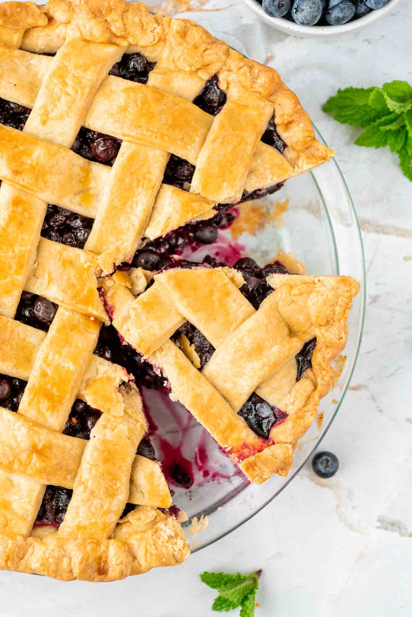 overhead shot of blueberry pie in a pie dish, with a slice of the pie, mint leaves on the side and some fresh blueberries