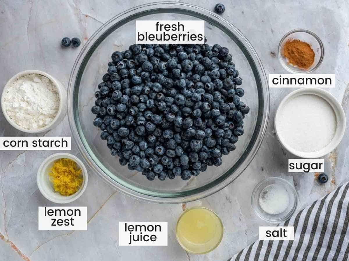 Ingredients needed to make blueberry pie filling including fresh blueberries, cornstarch, flour, cinnamon, lemon juice and zest, sugar and salt.