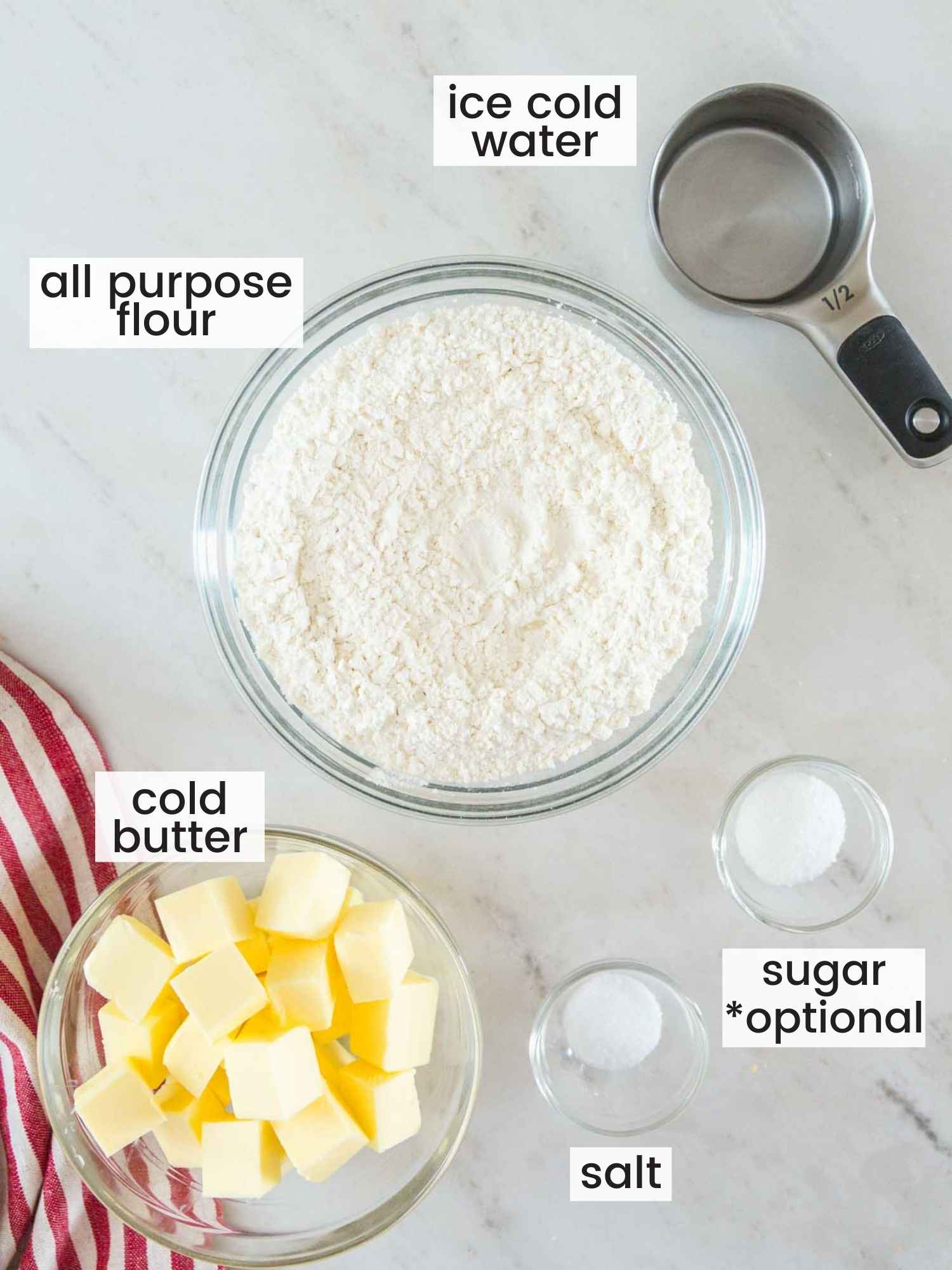 Ingredients needed to make butter pie crust including cold butter, flour, water, salt and sugar.