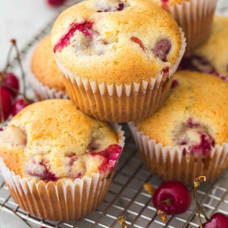 Cherry muffins placed and stacked on a wire rack with fresh cherries on the sides
