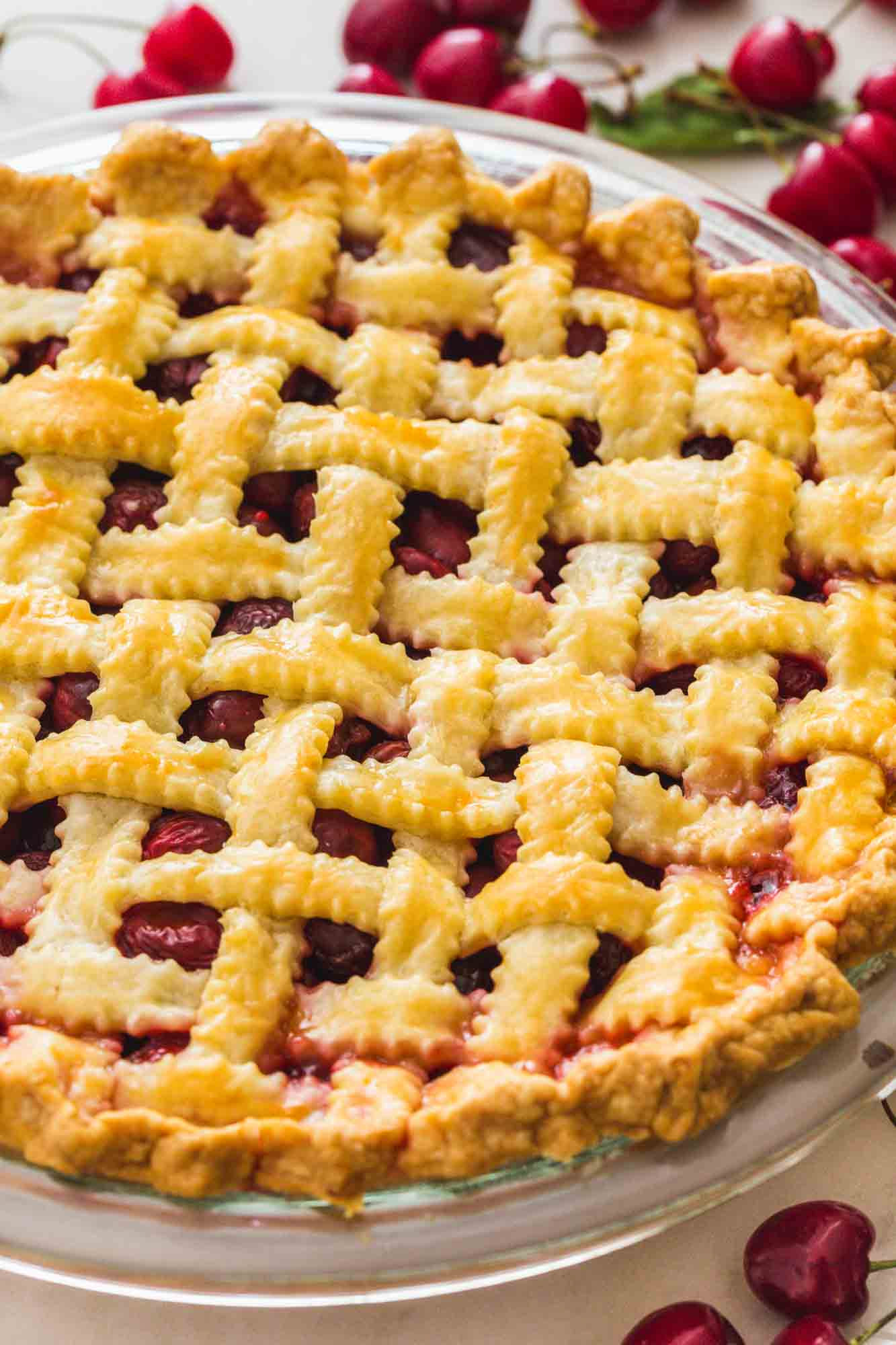 Cherry pie with lattice top, and fresh cherries on the sides