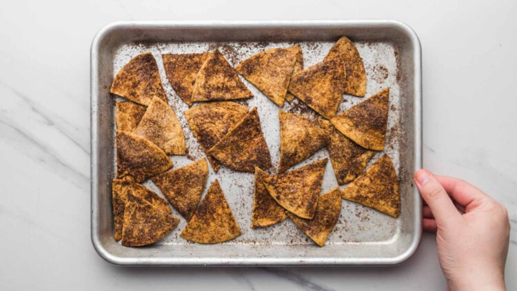 Baked cinnamon tortilla chips on a sheet pan