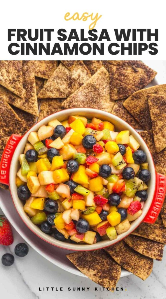 """Fruit salsa served in a red Le Creuset dish, with crunchy cinnamon chips on the sides served in a large white platter. With overlay text """"easy fruit salsa with cinnamon chips"""""""