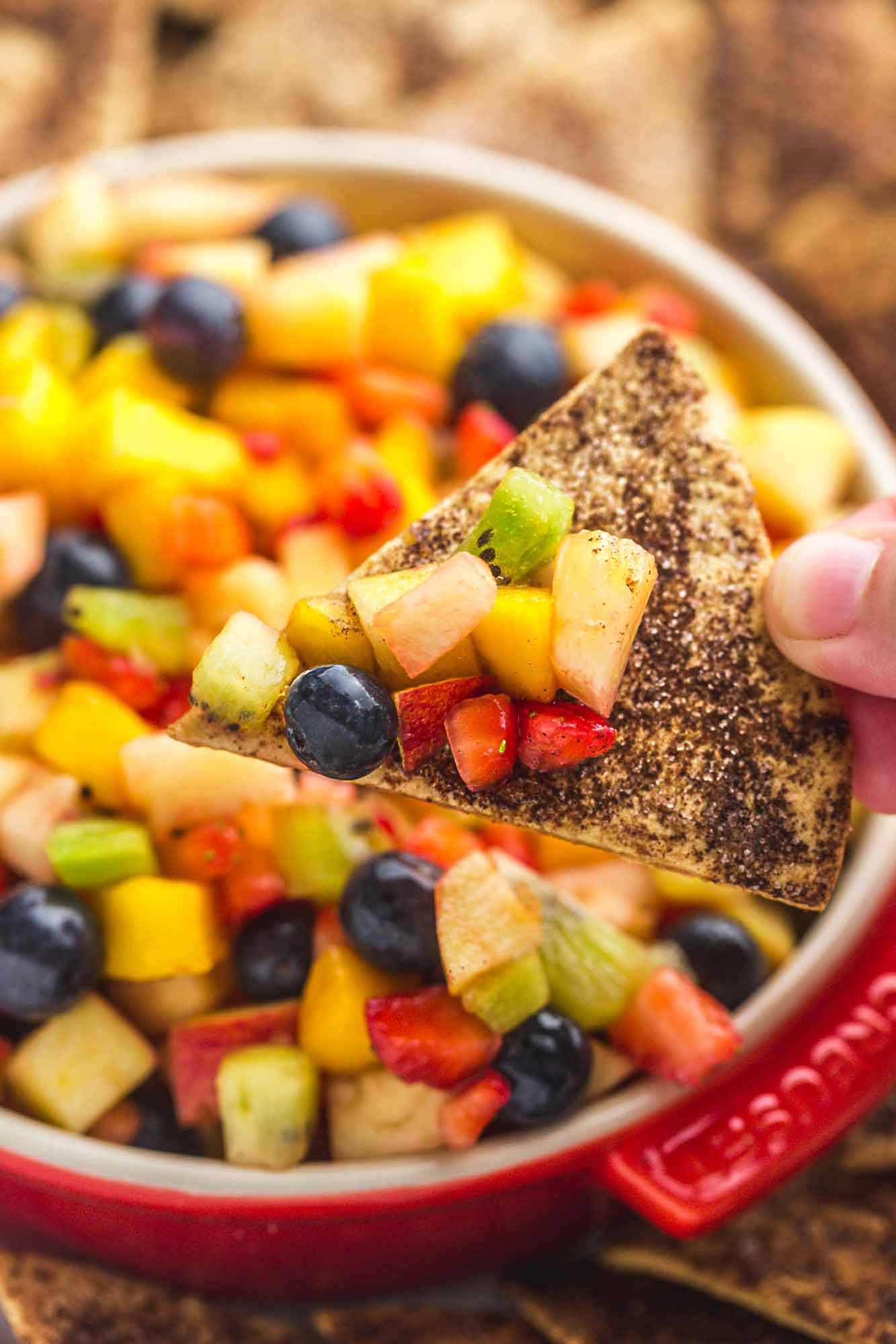 Fruit salsa served in a red Le Creuset dish, with crunchy cinnamon chips on the sides