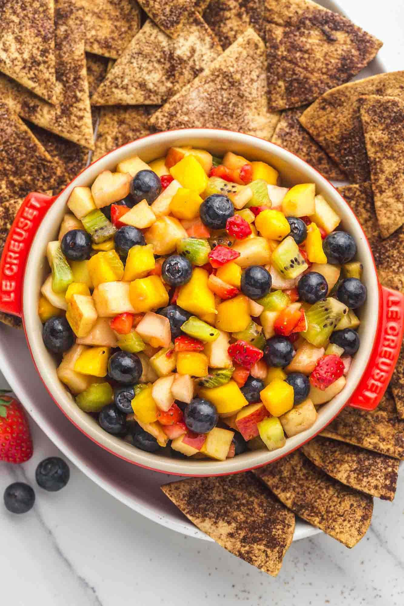 Fruit salsa served in a red Le Creuset dish, with crunchy cinnamon chips on the sides served in a large white platter.