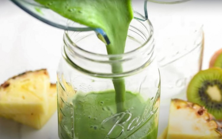 Pouring a green smoothie into a glass jar
