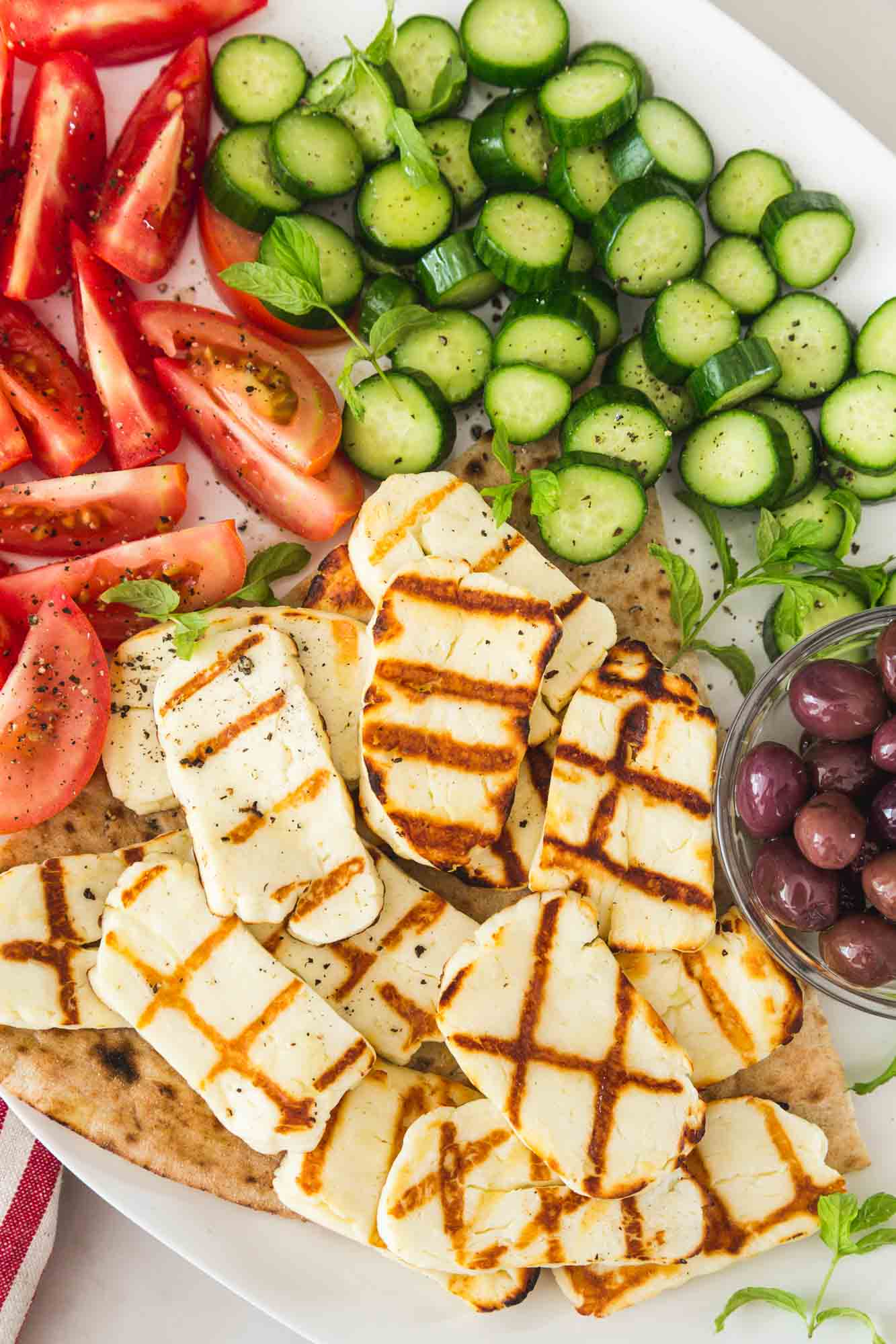 Overhead shot of grilled halloumi slices on a large white platter