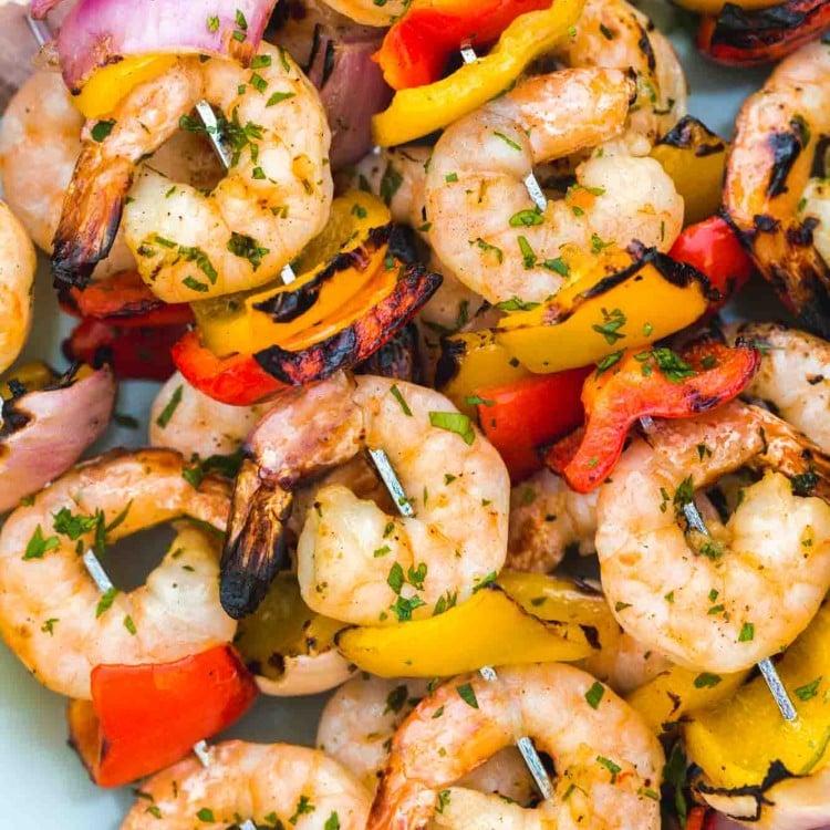 Grilled shrimp kabobs served on a blue platter, close up shot.