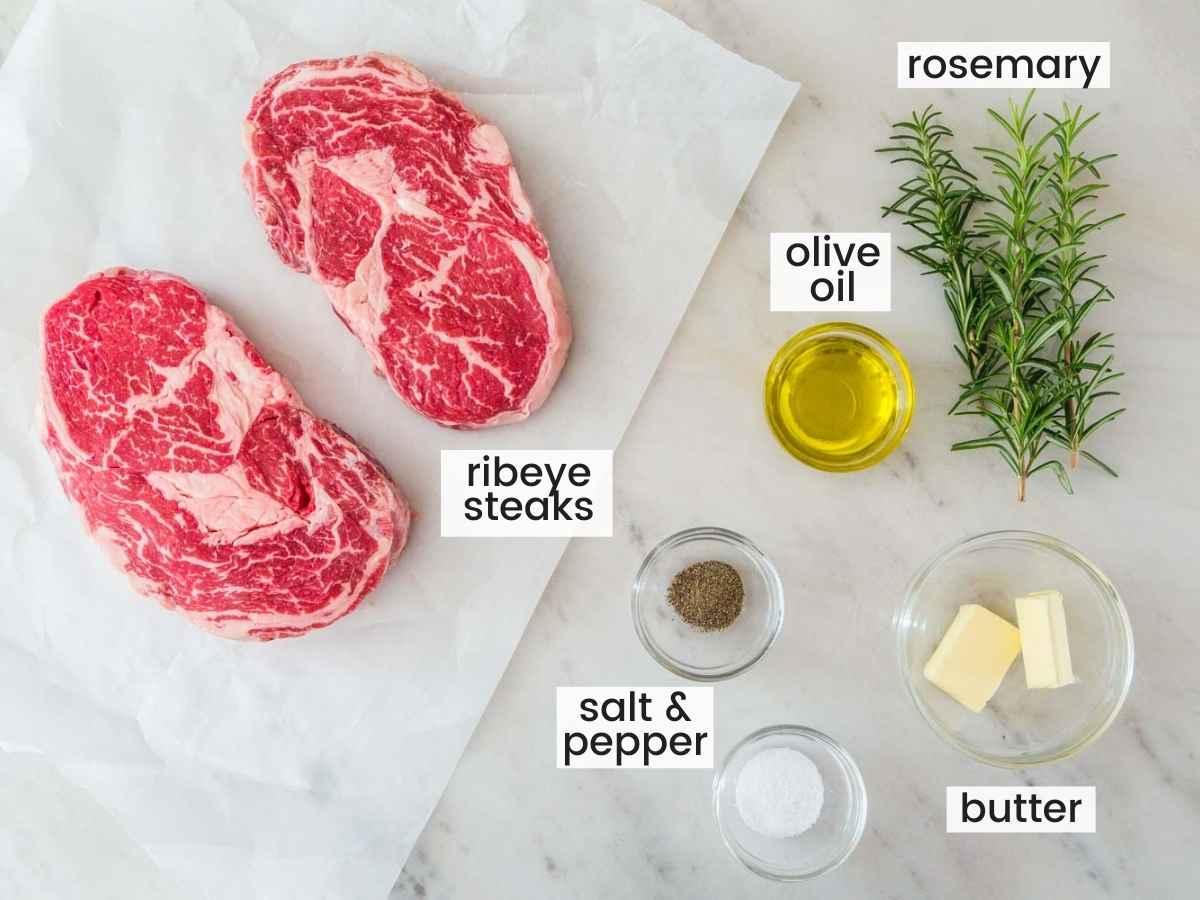 Ingredients needed for grilled steak, 2 ribeye steaks, fresh rosemary, olive oil, butter, salt, and pepper.