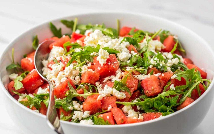 Horizontal image of a large salad bowl with watermelon and feta salad