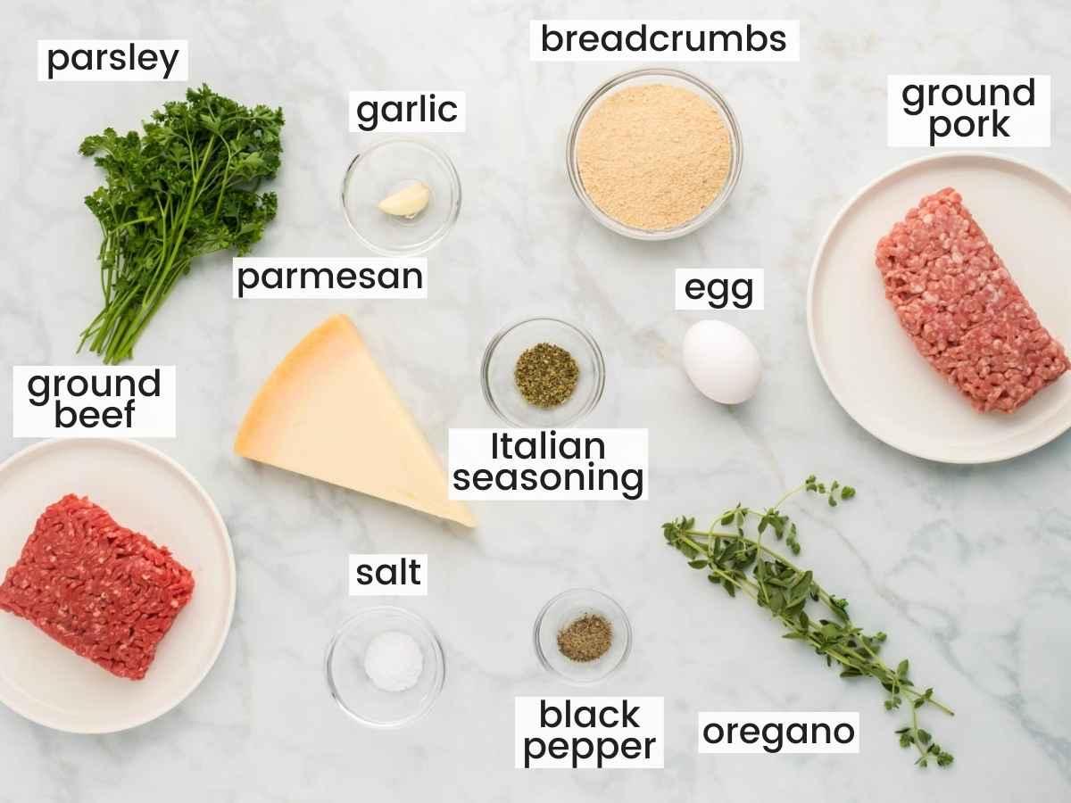 Ingredient shot for Italian meatballs including ground meat, parmesan, breadcrumbs, seasonings, and herbs.