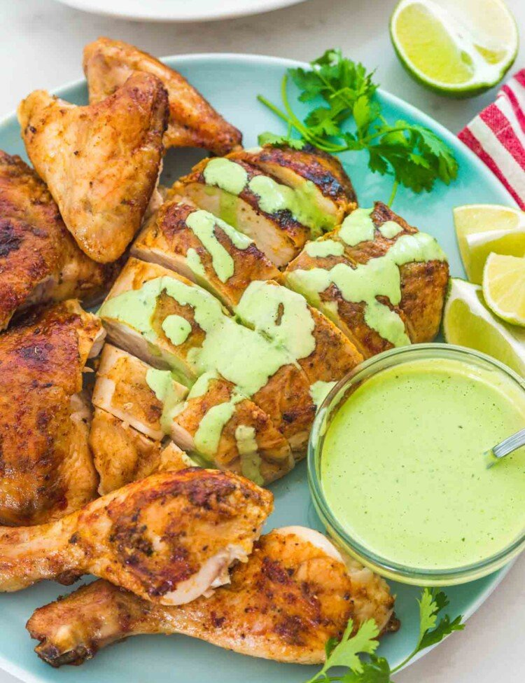 Carved Peruvian chicken on a plate with aji verde sauce on the side