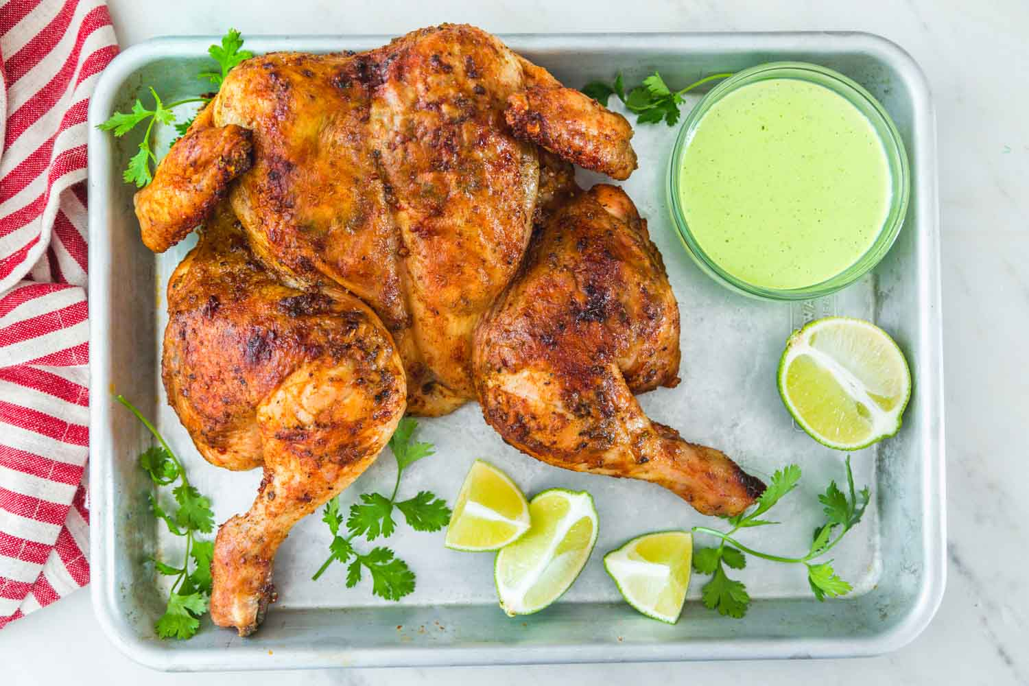 spatchcocked chicken on a sheet pan with aji verde sauce on the side