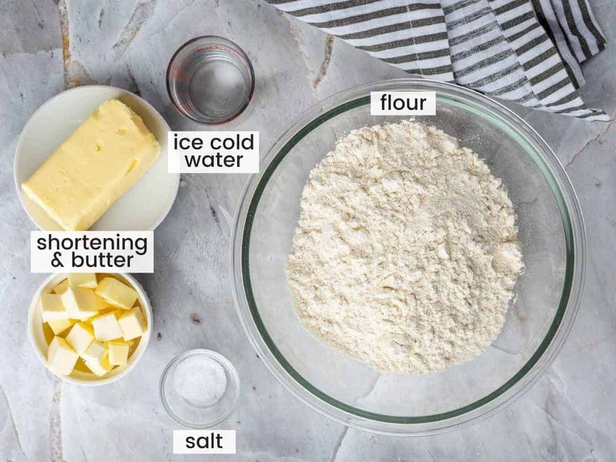Overhead shot of ingredients needed to make pie crust including flour, butter and shortening, water and salt.