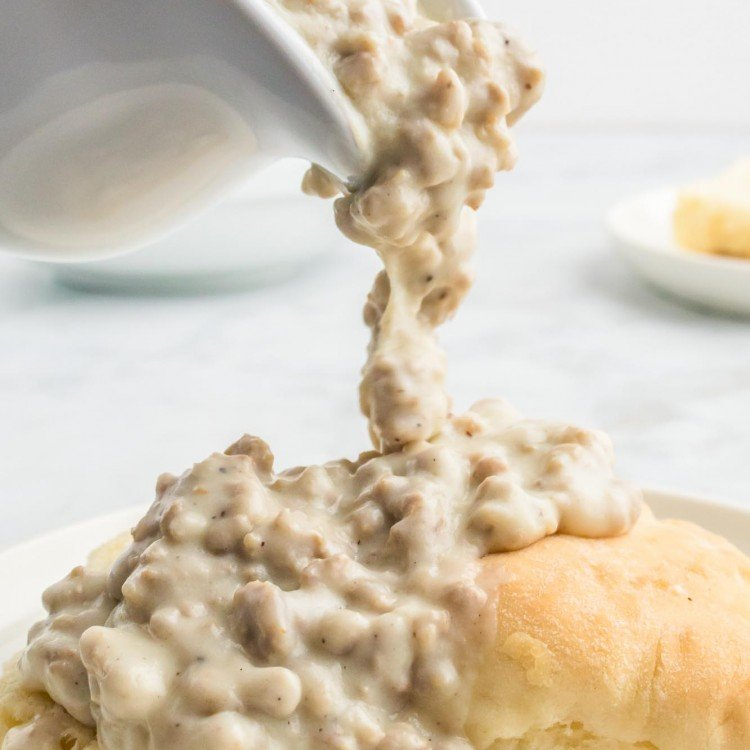 Pouring sausage gravy over biscuits