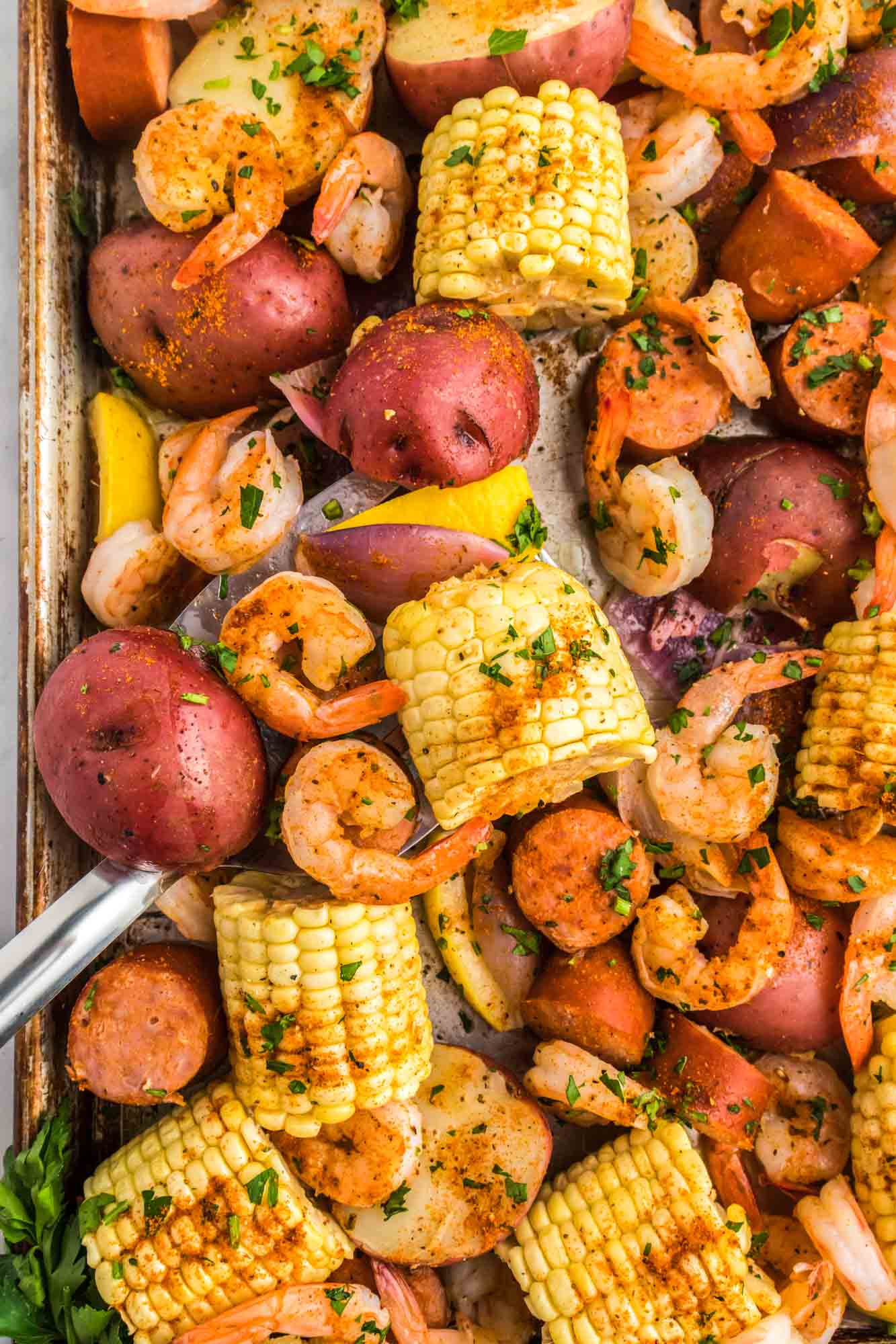 Overhead shot of shrimp boil on a sheet pan, garnished with fresh parsley leaves