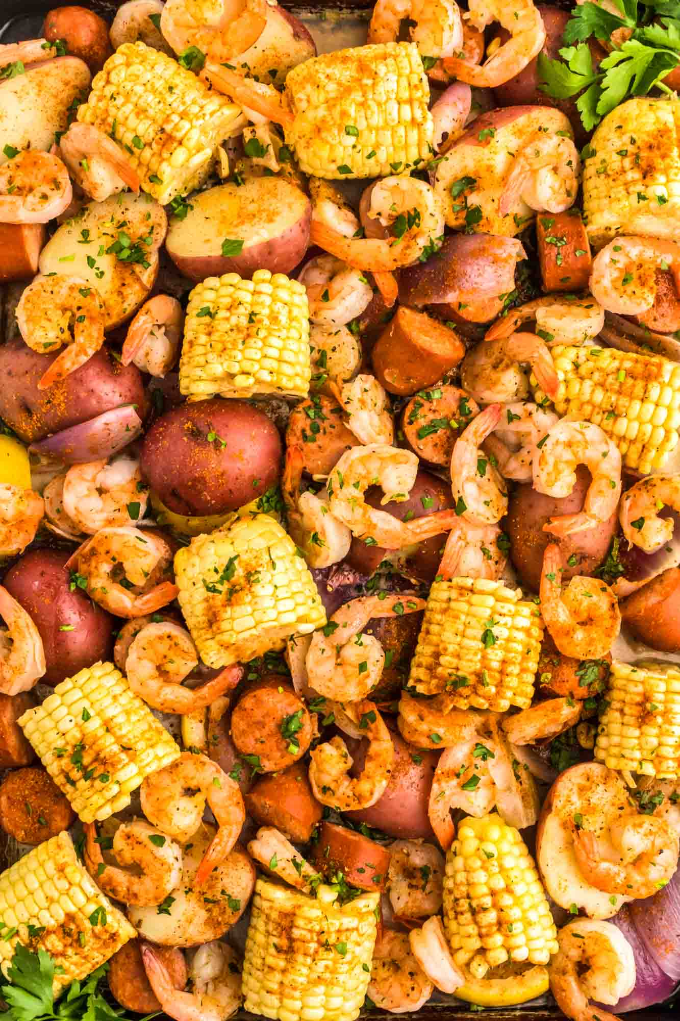 Overhead shot of shrimp boil including shrimp, corn, red potatoes, and onion. Served in a large sheet pan.
